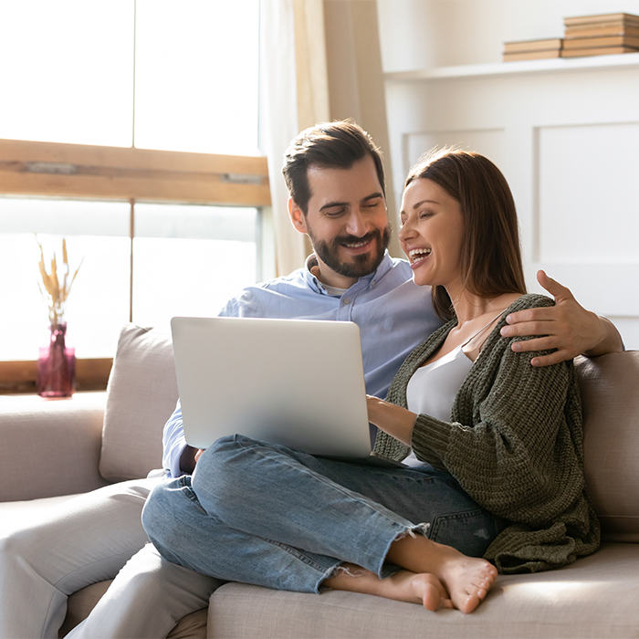 Couple on couch looking at laptop